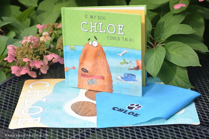 I See Me Personalized children's book, personalized dog bandana, and personalized dog placemat on table with flower bush in background
