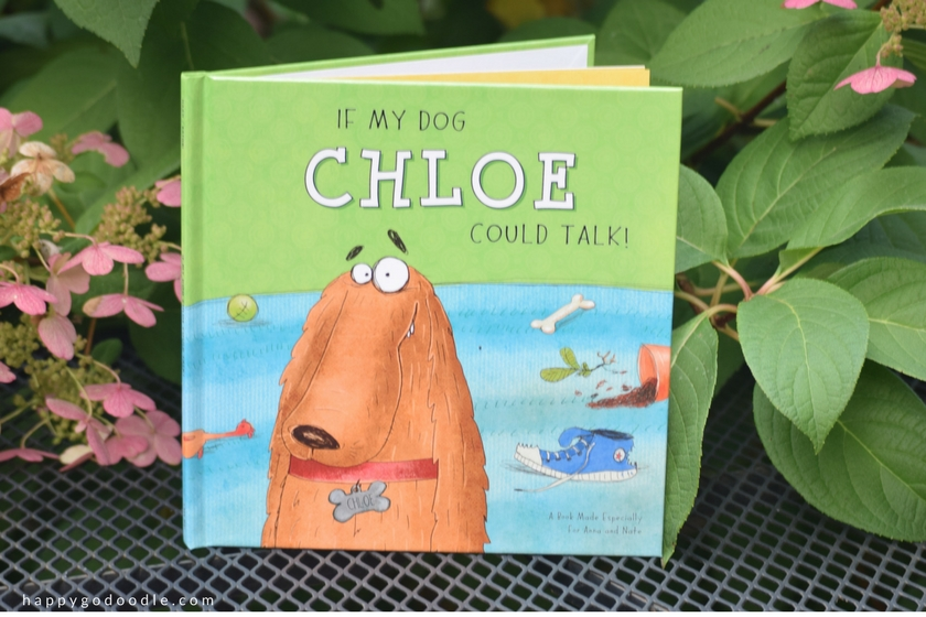 If My Dog Could Talk personalized book with red dog on cover. Book is sitting on table with green leaves and pink flowers around it